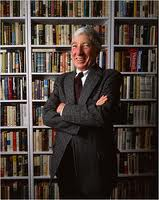 John Updike posed in front of bookshelves.